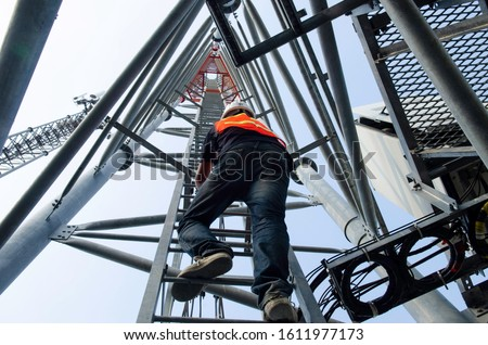 technician climb ladder for working on high telecommunication tower,worker wear Personal Protection Equipment for working high risk work,maintenance equipment on high tower.