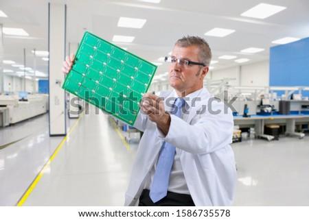 Technician Examining Printed Circuit Board In Electronics Factory