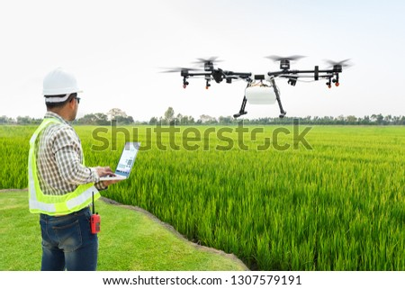 Technician farmer use wifi computer control agriculture drone fly to sprayed fertilizer on the rice fields, Smart farm 4.0 concept #1307579191