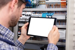 Technician Holding Digital Tablet With Blank Screen In Front Of Fuse Box
