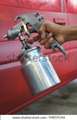 technician holding spray gun with painted car background