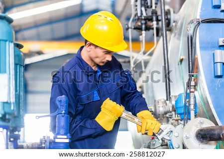 Technician in Asian factory at machine maintenance working with wrench #258812027