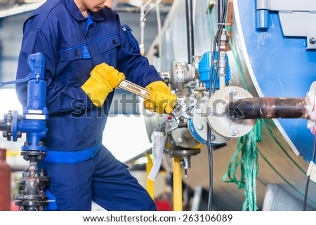 Technician in factory at machine maintenance working with wrench #263106089