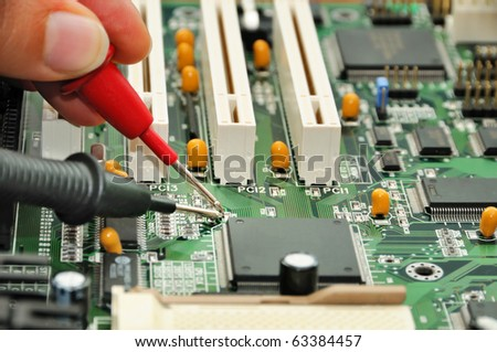 Technician in the service center testing electric circuit board