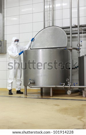 technician in white protective uniform,mask,goggles,gloves  opening large industrial process tank in factory
