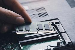 Technician install new RAM (Random-access memory) to memory slot on laptop motherboard