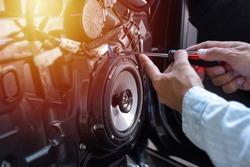 Technician installing the car speaker to the car door. Car audio installation concept.