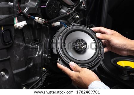Technician installing the car speaker to the car door. Car audio installation concept. Сток-фото ©