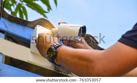 Technician installing wireless CCTV camera at house for security