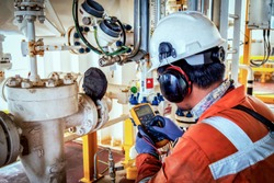Technician,Instrument technician on the job calibrate or function check on instrument device or level transmitter in oil and gas platform offshore.