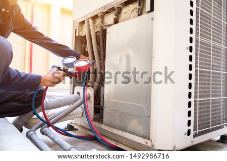 Technician is checking air conditioner ,measuring equipment for filling air conditioners. Photo stock ©