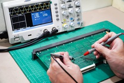 technician is inspecting the circuit board by digital storage oscilloscope