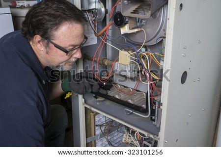 Technician  looking over a gas furnace with a flashlight before cleaning it.  ストックフォト ©