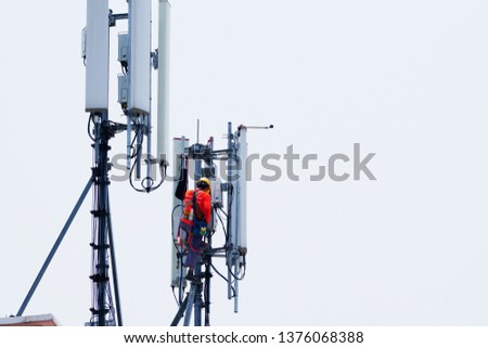 Technician maintenance on telecommunication tower doing ordinary maintenance & control to an antenna for communication, 3G, 4G and 5G cellular. Base Station or Base Transceiver Station. #1376068388