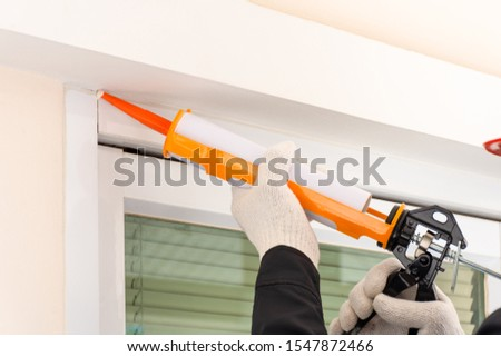 Technician man hand holding and using glue gun, silicone tube or manual caulking gun to seal the expansion joint between cement wall and the metal.
