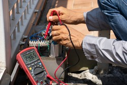Technician man hand using digital multimeter and checking the functional of auto door. Maintenance and repairing automatic gate concept. service concept.