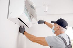 Technician man in medical mask worker repairing and installs air conditioner on white wall.