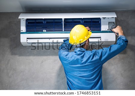 Technician man repairing ,cleaning and maintenance Air conditioner on the wall with screw driver in bedroom or office room.On site home service,Business ,Industrial concept. Foto stock ©