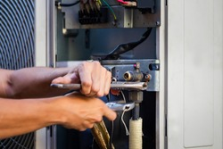 Technician man using a wrench fixing modern air conditioning system, Maintenance and repair concept
