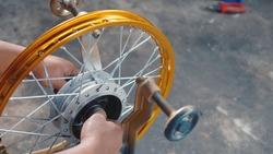 Technician man working motorcycle wheel has spokes weave up on mechanic new steel wheel, Motorcycle spokes wheel alignment machine tool