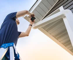 Technician on ladder installing and adjusting wireless security video camera underneath a roof for private house, monitor and recorder. Set up outdoor surveillance system. Safety and privacy concept.