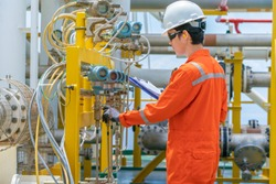 Technician operator checking and record reading value of pressure, temperature and flow transmitter in daily log book at offshore oil and gas central processing platform