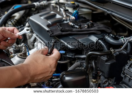 Technician Removing the gasoline  injector part in engine room check dust and test pressure in process maintenance concept