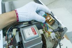 Technician repair microwave oven mainboard, Checking microwave oven mainboard, Home appliances repair service.