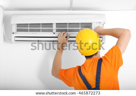 Technician repairing air conditioner on the wall #465872273