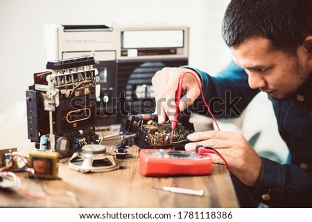 Technician repairing an old radio cassette recorder.