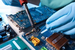 Technician repairing electronic circuit board with soldering iron at table, closeup