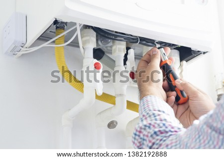 Technician repairing gas heater at home