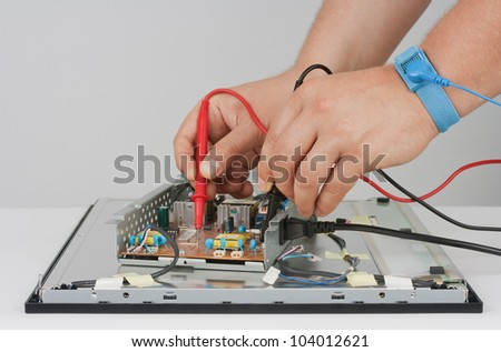 Technician repairing LCD Monitor. Objects photographed on a white background.