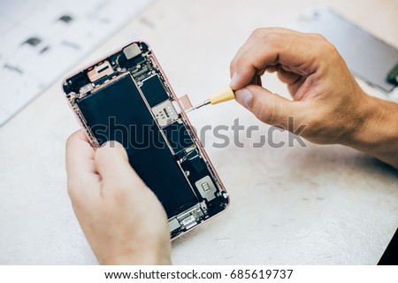 Technician repairs and inserts the sim memory card on the mobile phone in electronic smart phone technology service. Cellphone technology device maintenance engineer