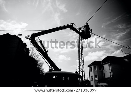 Technician's works in a bucket high up on a power pole. Traffic warning sign.