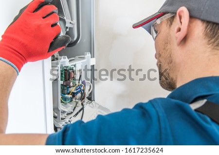 Technician Servicing Residential Heating Equipment. Central Heat Gas Furnace Issue.    ストックフォト ©