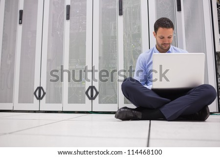 Technician sitting on floor working on laptop in data center - stock photo