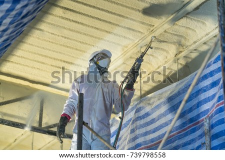 Shutterstock Technician spraying foam insulation using Plural Component Gun for polyurethane foam - Repair tool in the white protect suit applies a construction foam from the gun to the roof of a warehouse.