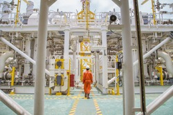 Technician walking through offshore oil and gas process for checking the condition of equipment on platform.