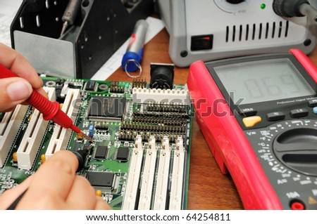 Technician with multimeter probes at his work place with soldering iron, multimeter and circuit board