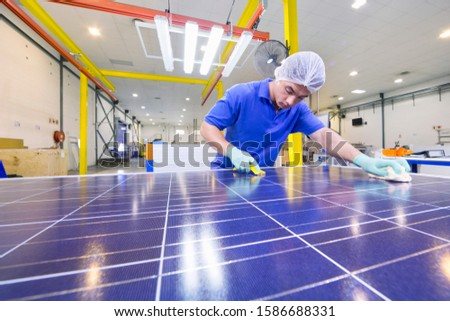Technician worker cleaning new solar panel on production line on factory floor