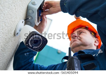 Technician worker installing video surveillance camera on wall