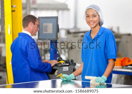 Technician worker smiling at camera cleaning and checking newly manufactured solar panels on production line