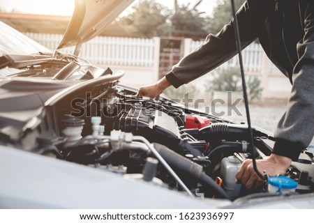 Technician working on checking and service car auto mechanic working in garage. Repair service.