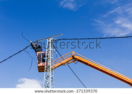 Technician works in a bucket high up on a power pole.