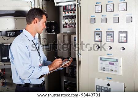 technician writing down modern computerized machine setting data