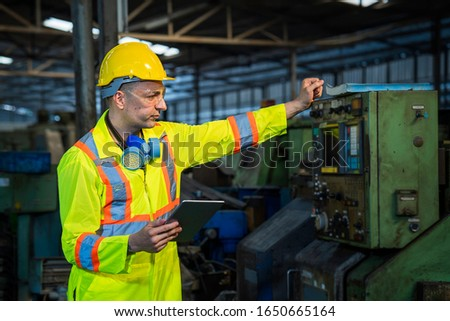 Technicians and engineers are working on machines in a factory. Caucasian man Mechanical Engineer holding tablet and checking equipment in the industrial.