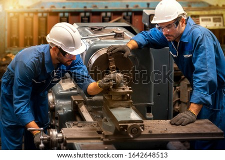 Technicians and engineers are working on machines in a factory. Twins Caucasian man Mechanical Engineer checking equipment in the industrial.