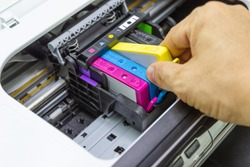 Technicians are install setup the ink cartridge of a inkjet printer the device of office automate for printing