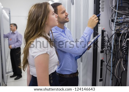 Technicians doing maintenance on servers with a clipboard
